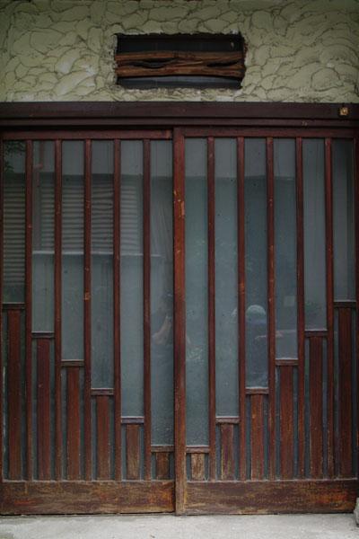 玄関の引き戸。階段状の板張りは裏側の入口と合わせたデザイン